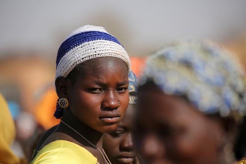 A displaced woman looks on while she waits for help at a village in Dablo area