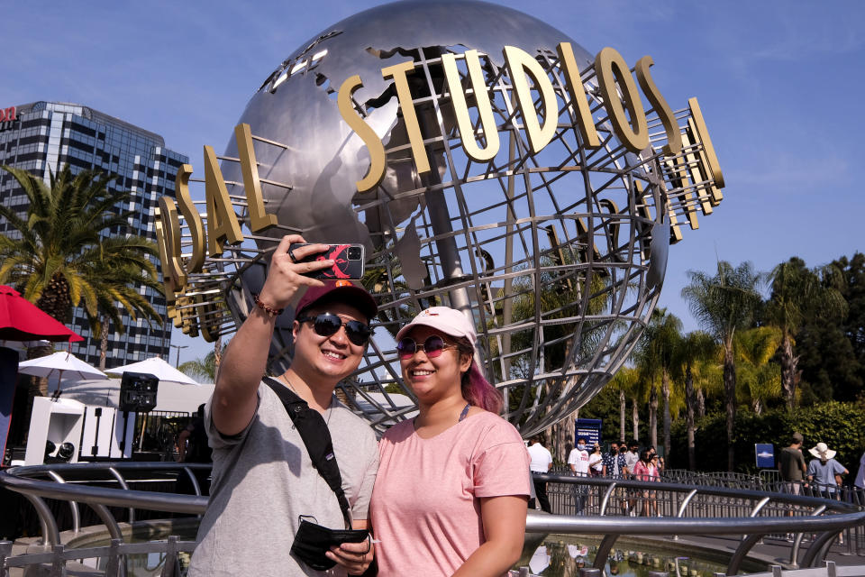 """People take photos at Universal Studios in Universal City, Calif., Tuesday, June 15, 2021. On Tuesday, California lifted most of its COVID-19 restrictions and ushered in what has been billed as the state's """"Grand Reopening."""" (AP Photo/Ringo H.W. Chiu)"""