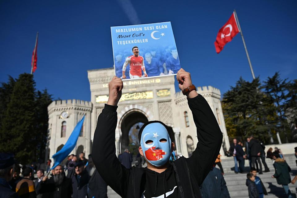 A supporter of China's Muslim Uighur minority holds a placard of Ozil during a demonstration in Istanbul in December 2019 (AFP via Getty Images)