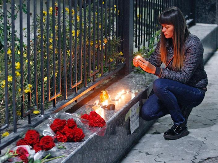 A woman lights a candle outside the Russian embassy in Kiev on October 31, 2015, to commemorate passengers that died in the crash of Kogalymavia flight 9268 (AFP Photo/Yury Kirnichny)