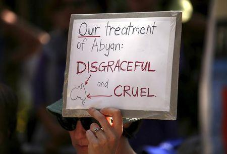 A protester holds a placard in support of refugees during a rally in central Sydney, Australia