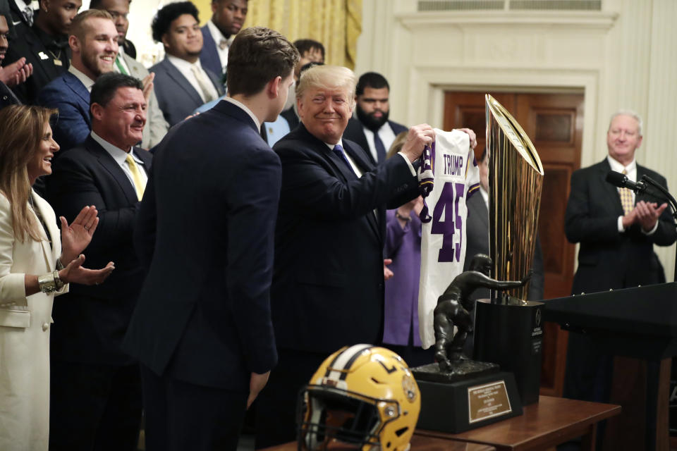 President Donald Trump is presented with a jersey from Louisiana State University Tigers quarterback Joe Burrow during an event to honor the 2019 NCAA football national champions, the Louisiana State University Tigers, in the East Room of the White House, Friday, Jan. 17, 2020, in Washington. (AP Photo/ Evan Vucci)