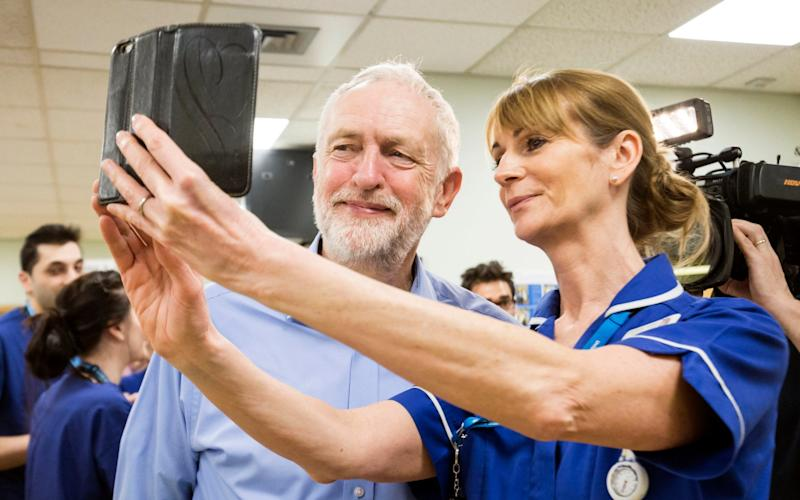 Jeremy Corbyn, the Labour leader poses for a selfie with a member of staff during a visit to Lincoln County Hospital - PA