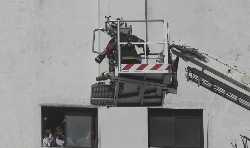People awaiting rescue stand near the window of a nine-story building with offices of a state-run telephone company during a fire in Mumbai, India, Monday, July 22, 2019. (AP Photo/Rafiq Maqbool)