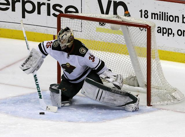 Minnesota Wild goalie Darcy Kuemper (35) deflects the puck against the Anaheim Ducks in the first period of an NHL hockey game in Anaheim, Calif., Tuesday, Jan. 28, 2014. (AP Photo/Reed Saxon)