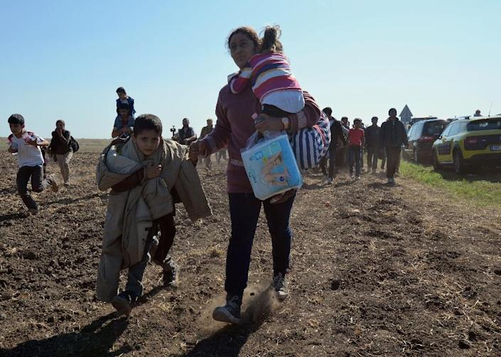 A family walks on a field after a crowd of refugees broke out of at collection point near Roszke village at the Hungarian-Serbian border on September 9, 2015 (AFP Photo/Csaba Segesvari)