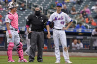 New York Mets catcher James McCann, left, and starting pitcher Jacob deGrom (48) stand with home plate umpire Manny Gonzalez, center, while waiting for the team trainer and manager before dGrom left the mound without throwing a pitch to a batter during the sixth inning of a baseball game against the Arizona Diamondbacks, Sunday, May 9, 2021, in New York. (AP Photo/Kathy Willens)