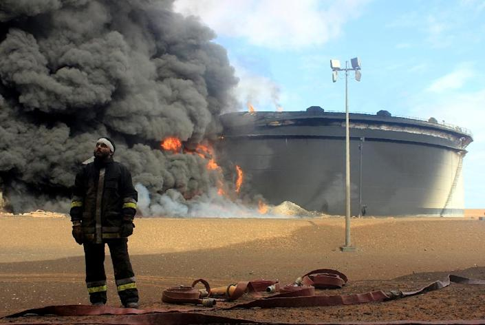 A Libyan fireman stands in front of smoke and flames rising from an oil storage tank at an oil facility in northern Libya's Ras Lanouf region on January 23, 2016 (AFP Photo/STRINGER)