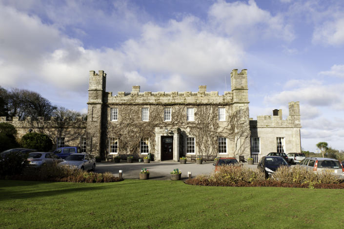 St Ives, United Kingdom - January 28, 2012: Tregenna Castle was built in 1774 by Samuel Stephens as a stately home. The castle is now a popular hotel and wedding venue. The image shows the front and entrance to the castle and the foreground green. Taken on a winters morning.