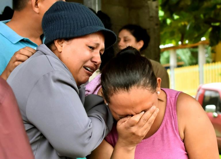 Relatives of inmates react after learning of their loved ones' fate in front of the prison in Tela, Honduras, where overnight rioting claimed at least 18 lives (AFP Photo/STR)