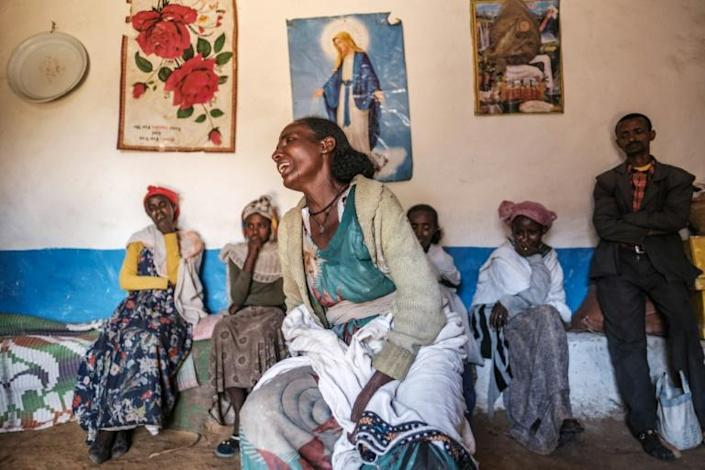 Beyenesh Tekleyohannes cries in her home as a group of relatives look on in the village of Dengolat, north of Mekele, the capital of Tigray, in February 2021
