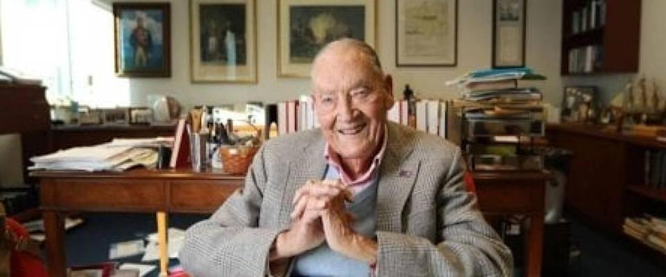 John Bogle poses for the camera, with a smile on his face and hands clasped.