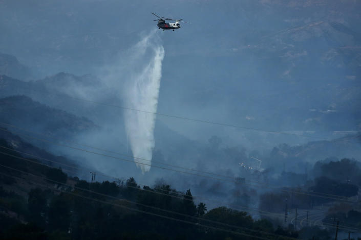 A helicopter drops water as the Bond Fire burns in Silverado, Calif., on Thursday, Dec. 3, 2020. (AP Photo/Ringo H.W. Chiu)
