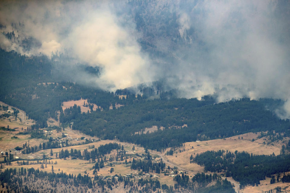 """FILE - In this Thursday, July 1, 2021 file photo, a wildfire burns in the mountains north of Lytton, British Columbia, Canada, during record high temperatures. According to a study released on Wednesday, July 7, 2021, the deadly heat wave that roasted the Pacific Northwest and western Canada """"was virtually impossible without human-caused climate change"""" which also added a few extra degrees to the record-smashing warmth. (Darryl Dyck/The Canadian Press via AP, File)"""
