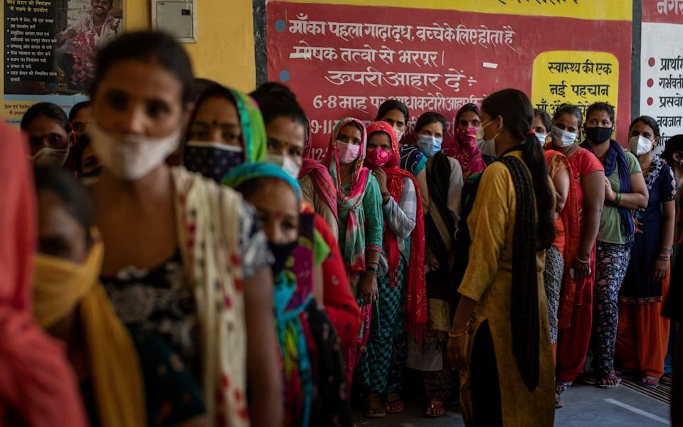 Women wait in line for the arrival of vaccines at a health centre in Noida, a suburb of New Delhi, India - AP