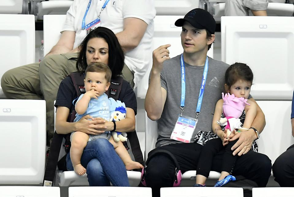 CORRECTS LOCATION - US actress Mila Kunis, left, and her husband US actor Ashton Kutcher, center, are seen with their children during the women's 3m synchro springboard final of the 17th FINA Swimming World Championships in the Hajos Alfred National Swimming Pool in Budapest, Hungary, Monday, July 17, 2017. (Tibor Illyes/MTI via AP)