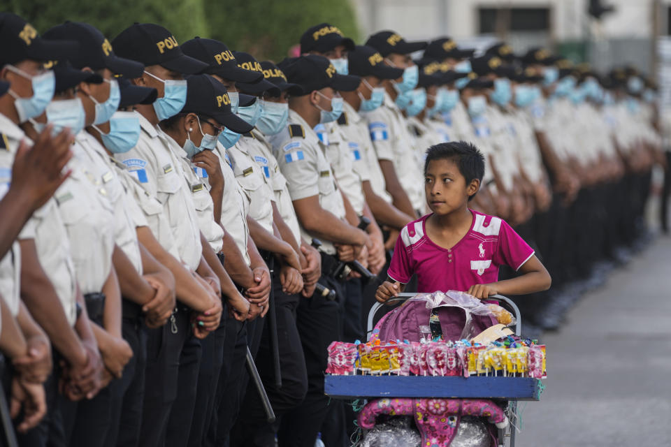 A teenager selling candy walks past police standing guard outside the National Palace where people rally in support of anti-corruption Prosecutor Juan Francisco Sandoval in Guatemala City, Saturday, July 24, 2021. Sandoval fled Guatemala late Friday, arriving in neighboring El Salvador just hours after he was removed from his post. (AP Photo/Moises Castillo)