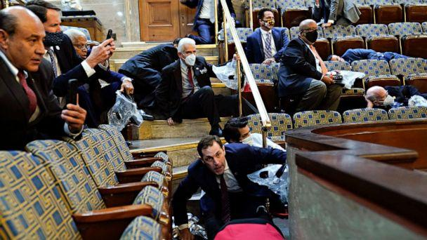 PHOTO: People shelter in the House gallery as protesters try to break into the House Chamber at the U.S. Capitol on Jan. 6, 2021, in Washington. (Andrew Harnik/AP)