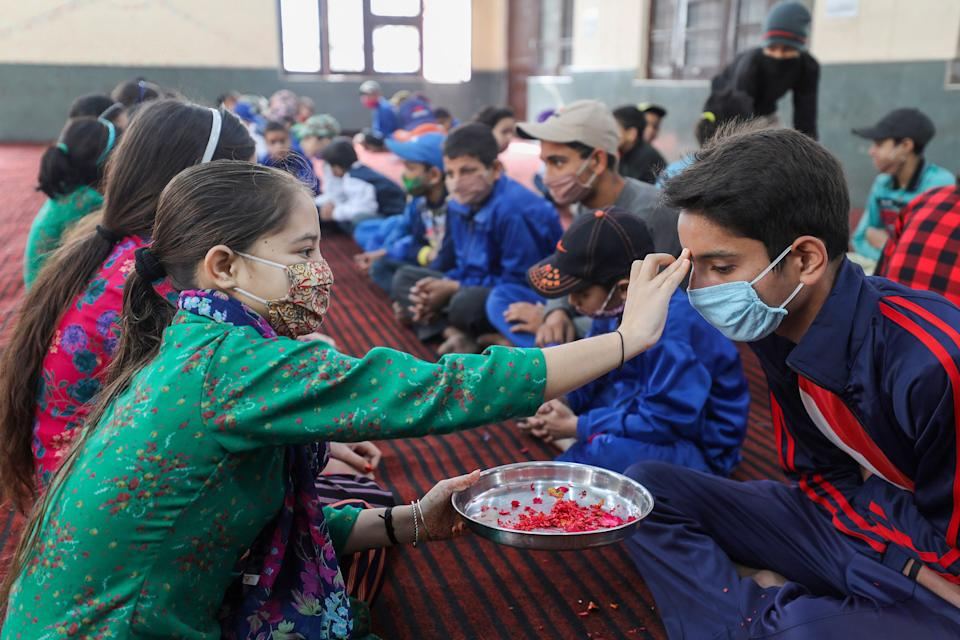 Girls put tika on the foreheads of boys on the occasion of the Bhai Dooj festival, at an orphanage in Jammu, Monday, 16 November.