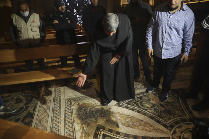 """A priest checks the damage after a man poured out flammable liquid at the Church of All Nations in the Garden of Gethsemane, in east Jerusalem, Friday, Dec. 4, 2020. Israeli police said Friday they arrested a Jewish man after he poured out a """"flammable liquid"""" inside a church near Jerusalem's Old City, in what they described as a """"criminal"""" incident. (AP Photo/Mahmoud Illean)"""