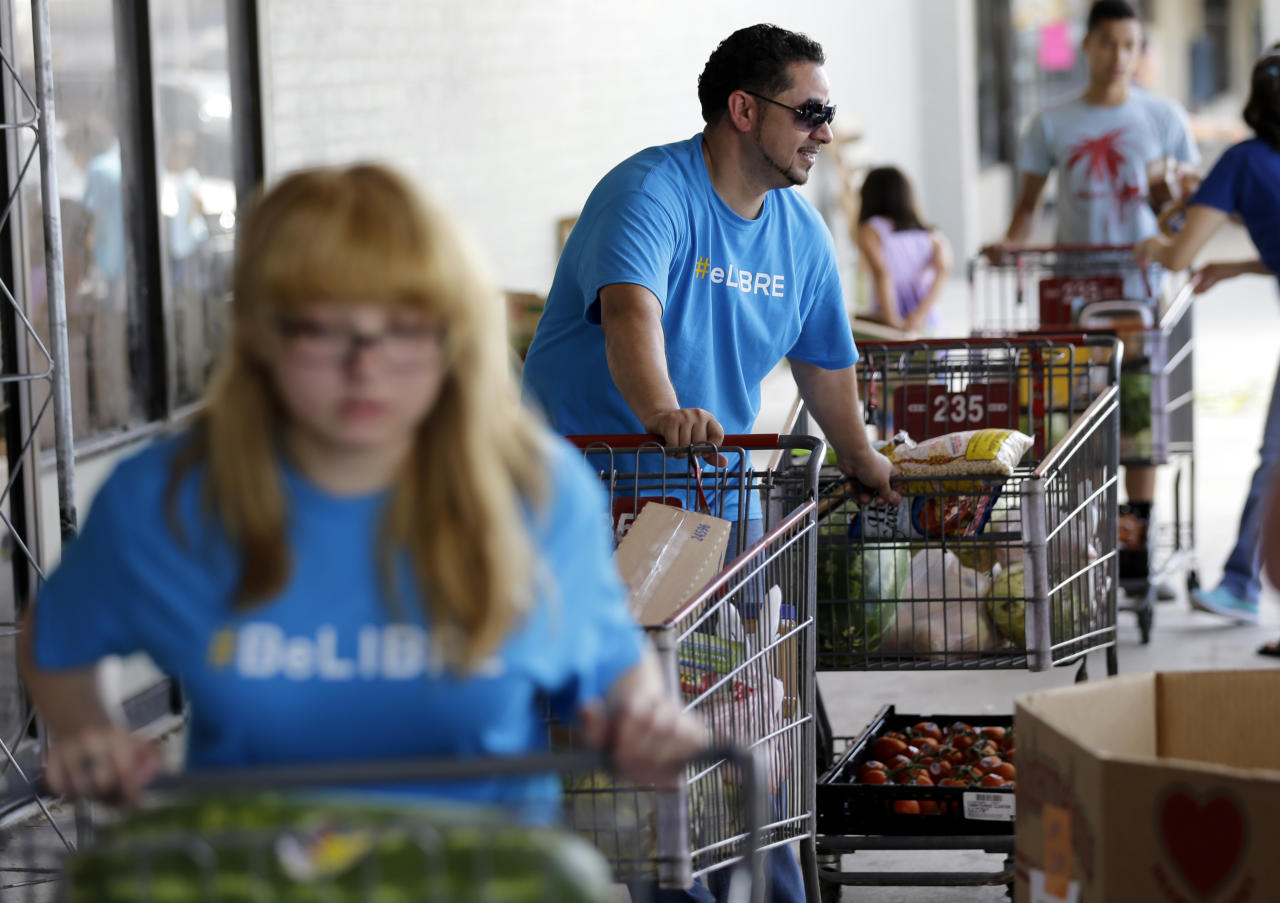 In this July 3, 2014 photo, pastor Marcus Burgos, center, and other volunteers load groceries at a food bank at the Abundant Life Church in San Antonio. The food bank is cosponsored by the Libre Initiative, partly funded by conservative billionaires Charles and David Koch, which is looking to make inroads with the rising voting block of Hispanics. (AP Photo/Eric Gay)