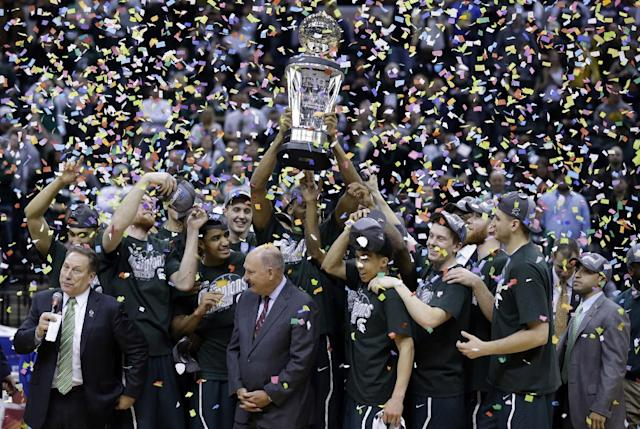 Michigan State players and coaches celebrate with the championship trophy after defeating Michigan 69-55 in an NCAA college basketball game in the championship of the Big Ten Conference tournament on Sunday, March 16, 2014, in Indianapolis. (AP Photo/Michael Conroy)