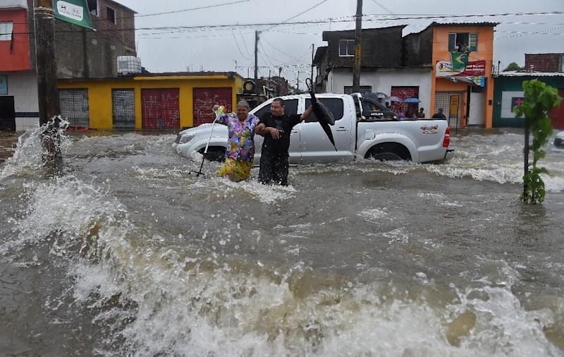 People attempt to make their way through a flooded avenue during torential rain in Recife, Brazil, June 26, 2014