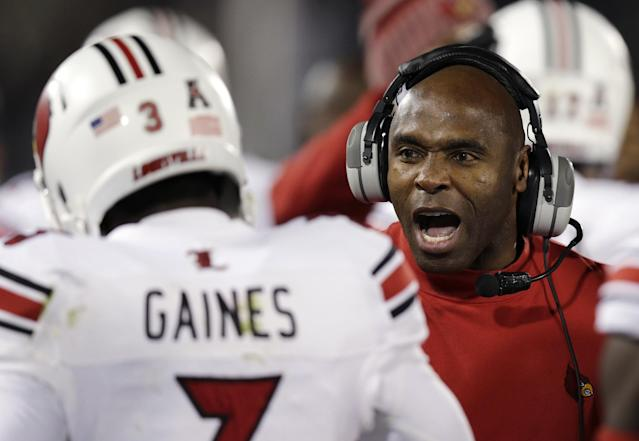 Louisville head coach Charlie Strong, right, congratulates Louisville cornerback Charles Gaines during the first half of an NCAA college football game, in East Hartford, Conn., Friday, Nov. 8, 2013. (AP Photo/Charles Krupa)