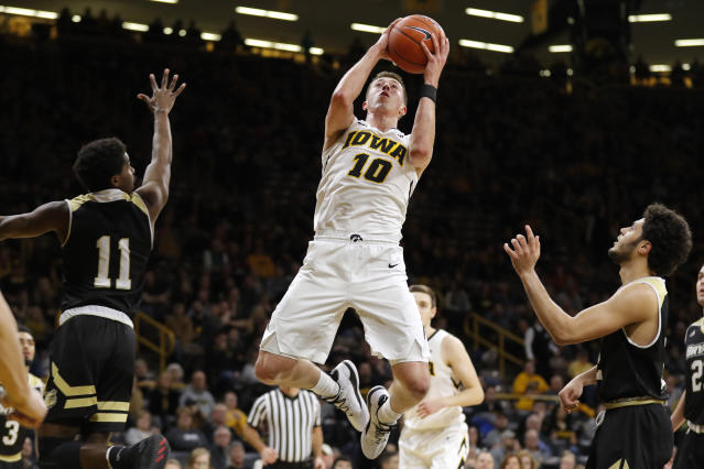 Iowa guard Joe Wieskamp (10) drives to the basket between Bryant's Adam Grant, left, and Joe Kasperzyk, right, during the second half of an NCAA college basketball game Saturday, Dec. 29, 2018, in Iowa City, Iowa. Iowa won 72-67. (AP Photo/Charlie Neibergall)