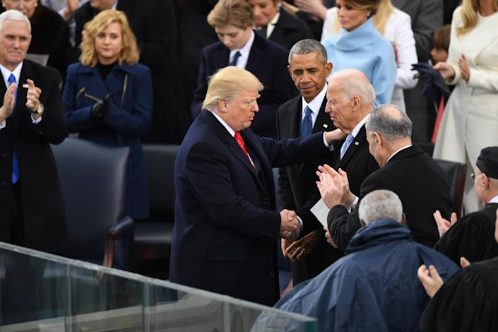 President Donald J. Trump shakes hands with Former vice president Joe Biden as Former president Barack Obama looks on at the inauguration of President Donald J. Trump on January 20, 2017. (Photo by Jonathan Newton /The Washington Post via Getty Images)