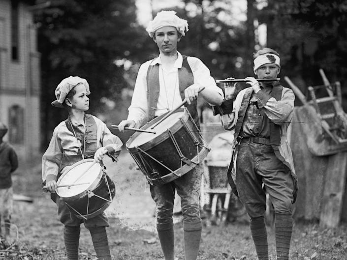 Three boys carry instruments while dressed in colonial clothing to celebrate July 4, circa 1922.