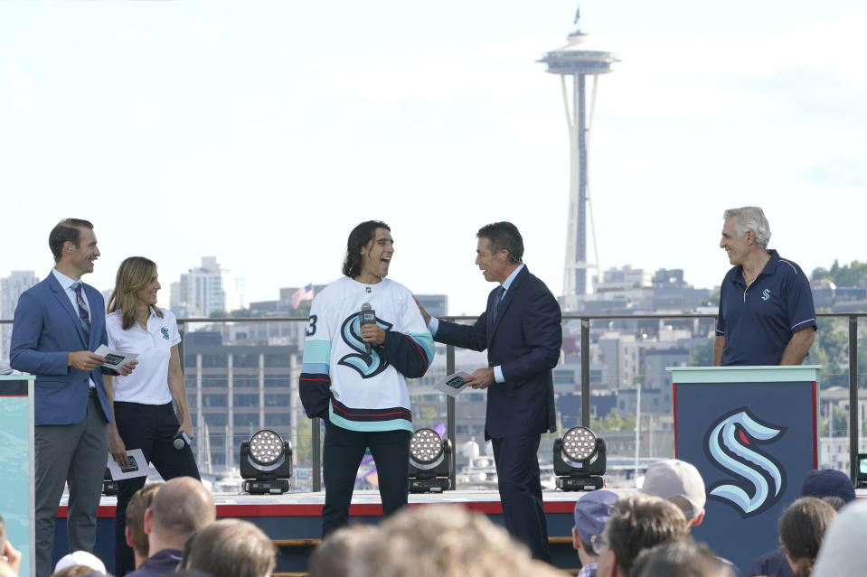 Brandon Tanev, center, a forward from the Pittsburgh Penguins, is introduced as a player for the Seattle Kraken, Wednesday, July 21, 2021, during the Kraken's NHL hockey expansion draft event in Seattle. Looking on are ESPN hosts Dominic Moore, left, and Chris Fowler, second from right, and Kraken general manager Ron Francis, right, and Kraken scout Cammi Granato, second from left. (AP Photo/Ted S. Warren)