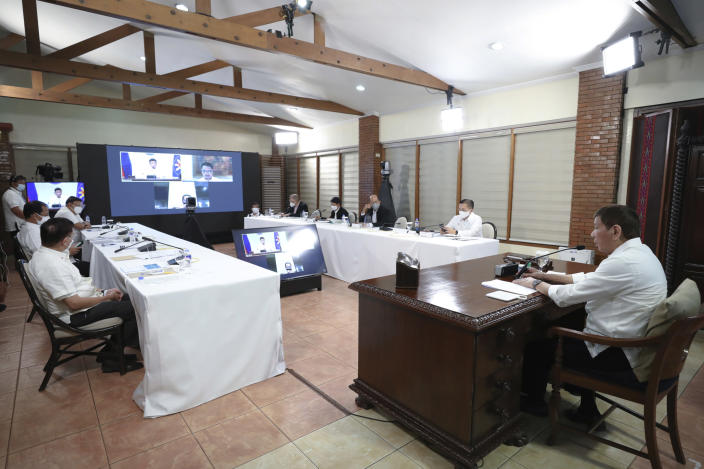 In this photo provided by the Malacanang Presidential Photographers Division, Philippine President Rodrigo Duterte, right, presides over a meeting with the Inter-Agency Task Force on the Emerging Infectious Diseases (IATF-EID) core members at the Malacanang presidential palace in Manila, Philippines Wednesday, May 5, 2021. The Philippine president has asked China to get back 1,000 doses of donated Sinopharm vaccine after facing criticisms for allowing himself to be injected with it although it has not yet been authorized for public use in the country. (Alberto Alcain/Malacanang Presidential Photographers Division via AP)