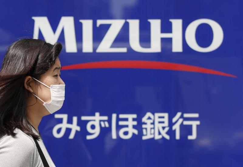A woman walks past a branch of Mizuho bank, belonging to Mizuho Financial Group, in Tokyo July 31, 2013. REUTERS/Issei Kato