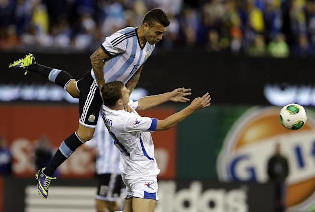 Argentina's Nicolas Otamendi, top, heads the ball away from Bosnia's Edin Dzeko during the first half of an international friendly soccer match Monday, Nov. 18, 2013, in St. Louis. (AP Photo/Jeff Roberson)
