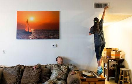 FILE PHOTO: Leanne Bell, 39, checks the air quality of a vent as her husband, Spc. Tevin Mosley, 26, looks on while waiting for a maintenance crew to arrive at the army base housing allocated to the family in Fort Hood, Texas, U.S on May 16, 2019. The family says they began suffering breathing issues, depression, and rashes they attribute to a mold infestation and were forced to vacate the home in March after it was put under quarantine while repairs were made. Despite the repairs, mold can visibly be seen on surfaces throughout the home. REUTERS/Amanda Voisard