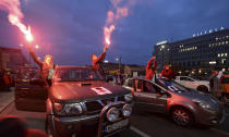 Angered women's rights activists and their supporters block rush-hour traffic at a major roundabout on the fifth day of nationwide protests against recent court ruling that tightened further Poland's restrictive abortion law, in Warsaw, Poland, on Monday, Oct. 26, 2020. The court effectively banned almost all abortions. (AP Photo/Czarek Sokolowski)