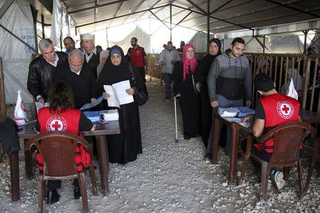 Syrian refugees line up to receive aid for the winter from the UN refugee agency (UNHCR) in Tripoli, northern Lebanon