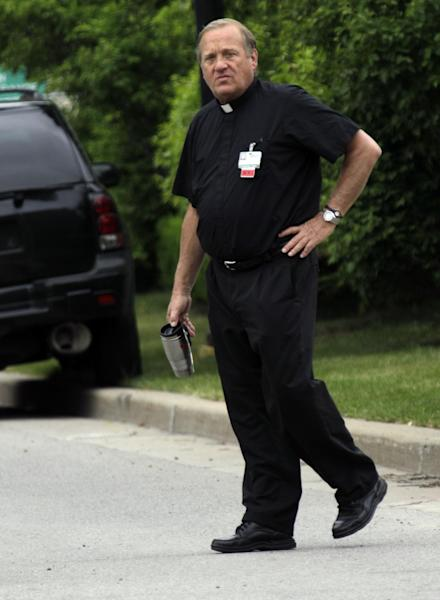 "A priest walks near the scene of a shooting at Erie Count Medical Center in Buffalo, N.Y., Wednesday, June 13, 2012. A police official confirms that a woman was killed Wednesday morning on the grounds of the Erie County Medical Center, which he describes as being in ""complete lockdown"" as SWAT teams and other officers cordon off the 65-acre campus.(AP Photo/David Duprey)"