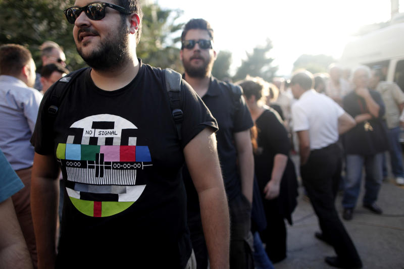 A supporter looks on outside the Greek state television ERT headquarters after the government's announcement that it will shut down the broadcaster in Athens, Greece, Tuesday, June 11, 2013. Greece is to close down all its state-run TV and radio stations with the loss of some 2,500 jobs as part of its cost-cutting drive demanded by the bailed-out country's international creditors. Tuesday's move heralds the first direct public sector layoffs in more than three years of painful austerity, which have cost about a million private sector jobs. (AP Photo/Petros Giannakouris)