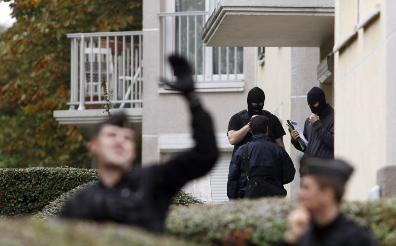 """French police officers converse outside a building where authorities discovered bomb-making material after the break up of a suspected terrorist cell last week, in Torcy, east of Paris, Wednesday, Oct. 10, 2012. French police discovered bomb-making materials in an underground parking lot near Paris as part of a probe of an """"extremely dangerous terrorist cell"""" linked to an attack on a kosher grocery, a state prosecutor said Wednesday. (AP Photo/Thibault Camus)"""