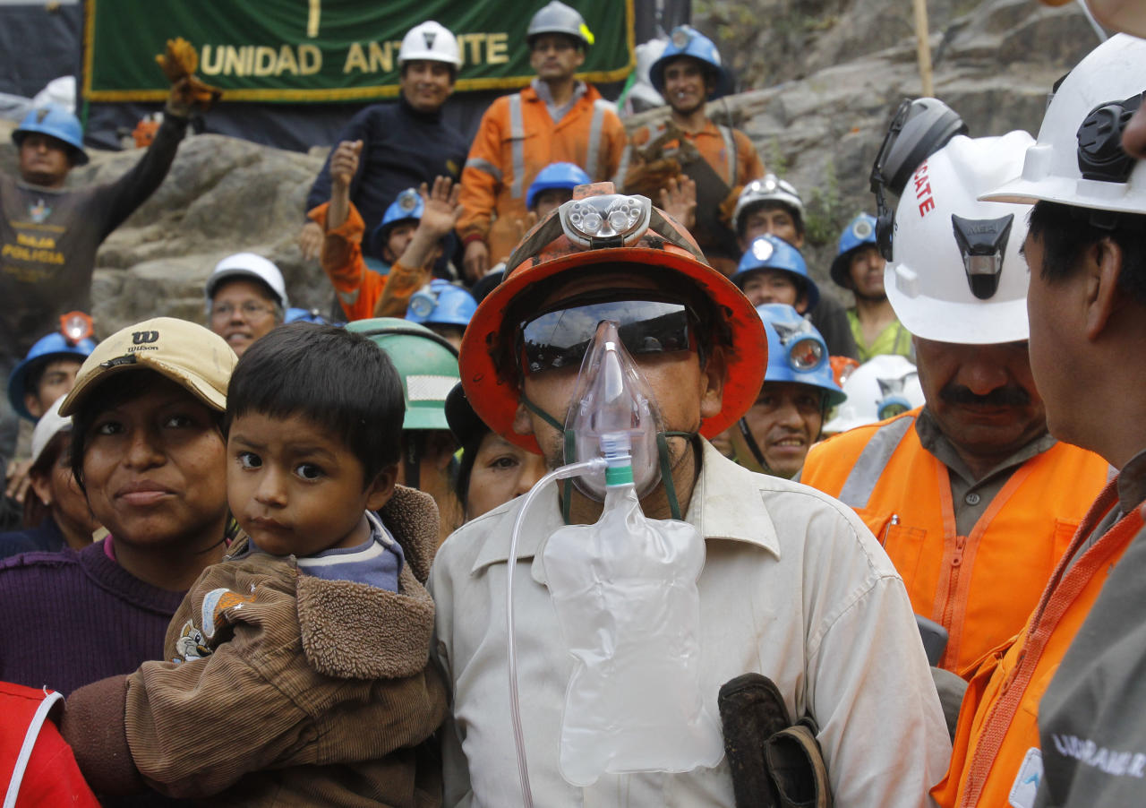 ** CORRECTS TO REMOVE EXTRANEOUS LAST SENTENCE ** Miner Jacinto Pariona, center right, stands with his family after he was the first miner to be rescued from the Cabeza de Negro gold-and-copper mine in Yauca del Rosario, Peru, Wednesday April 11, 2012. Nine miners had been trapped inside a wildcat mine since April 5. (AP Photo/Martin Mejia)