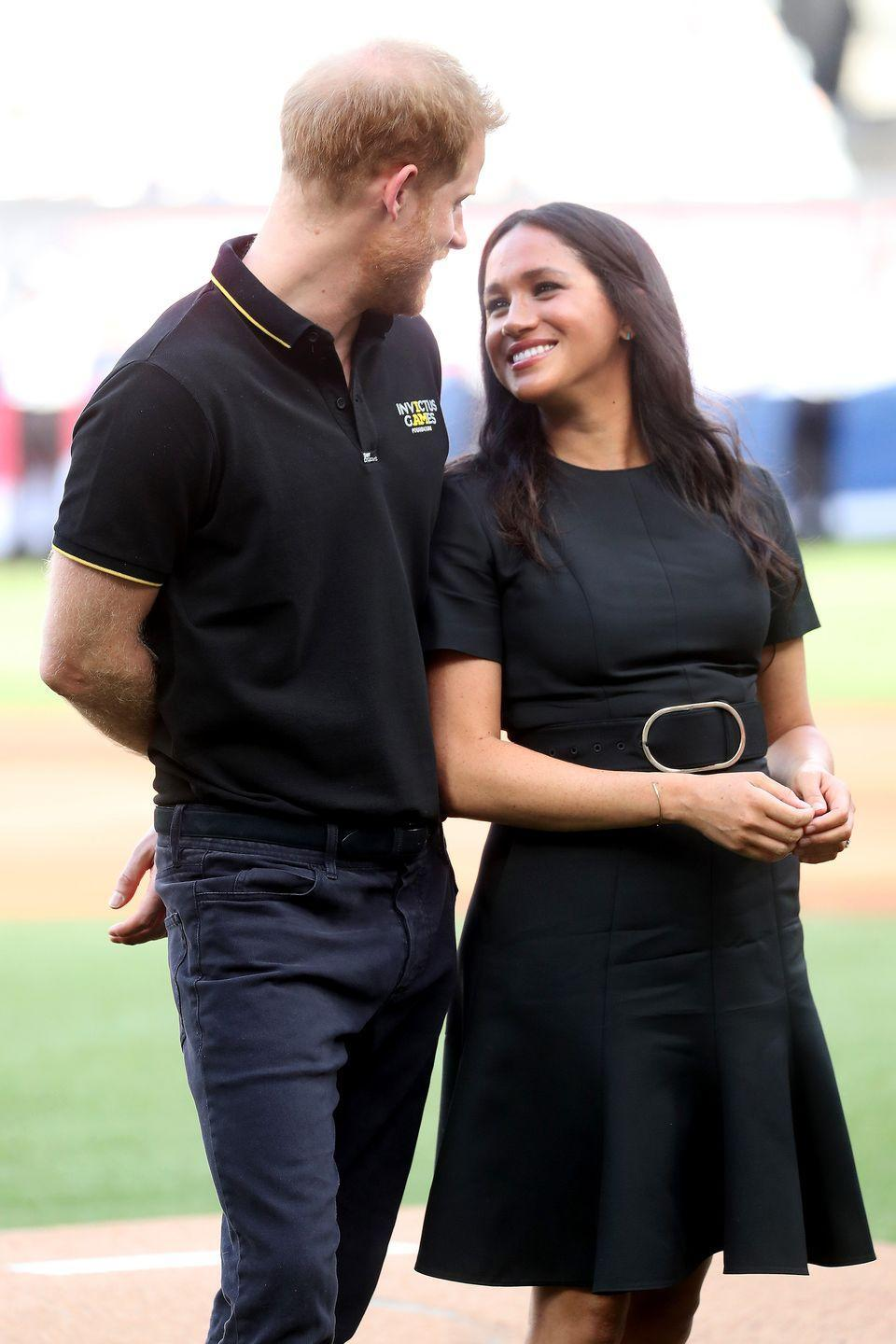 <p>Meghan smiles as she leans against Harry during the Boston Red Sox against the New York Yankees match at the London Stadium.</p>