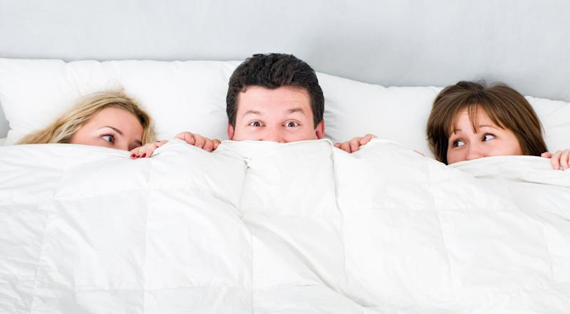 man lying with two girls in bed