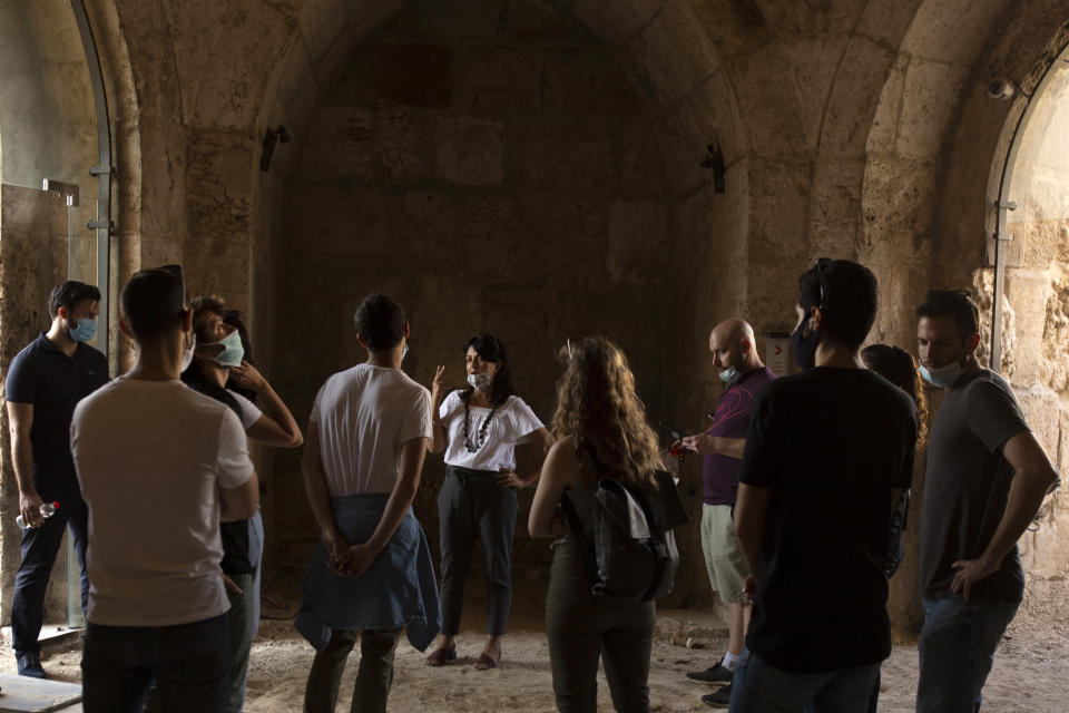 Eilat Lieber, center, Director and Chief Curator of the Tower of David Museum, leads a tour, in the Old City of Jerusalem, Wednesday, Oct. 28, 2020. The ancient citadel is devoid of tourists due to the pandemic and undergoing a massive restoration and conservation project. (AP Photo/Maya Alleruzzo)