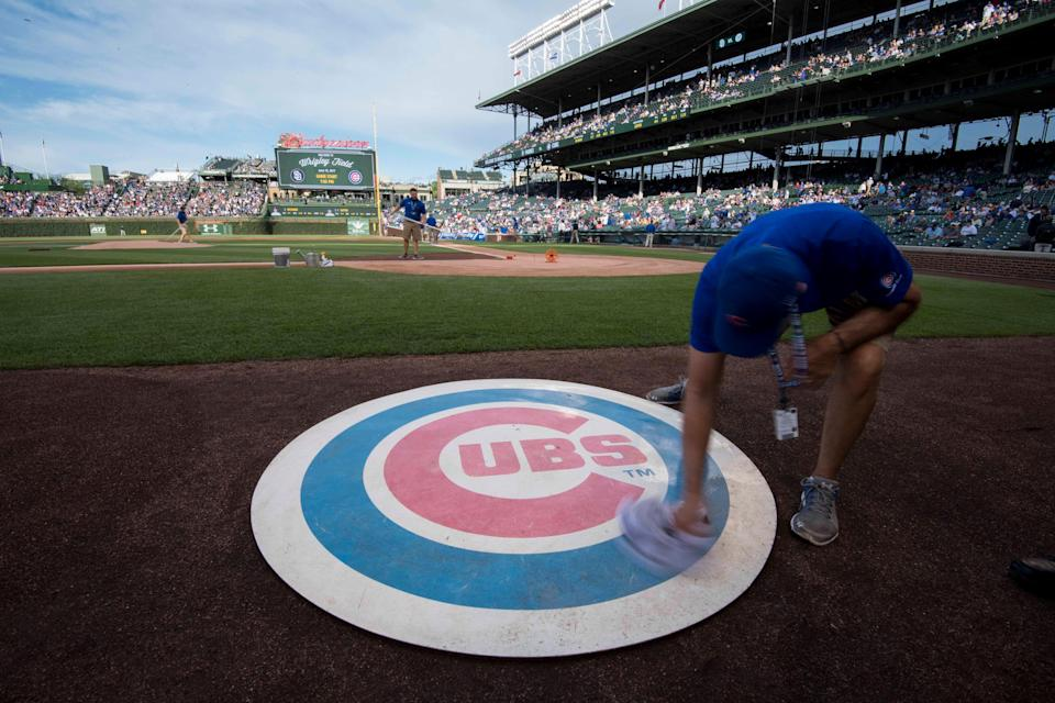 Jun 19, 2017; Chicago, IL, USA; A member of the grounds crew wipes off the Chicago Cubs' on deck logo prior to a game against the San Diego Padres at Wrigley Field. Mandatory Credit: Patrick Gorski-USA TODAY Sports