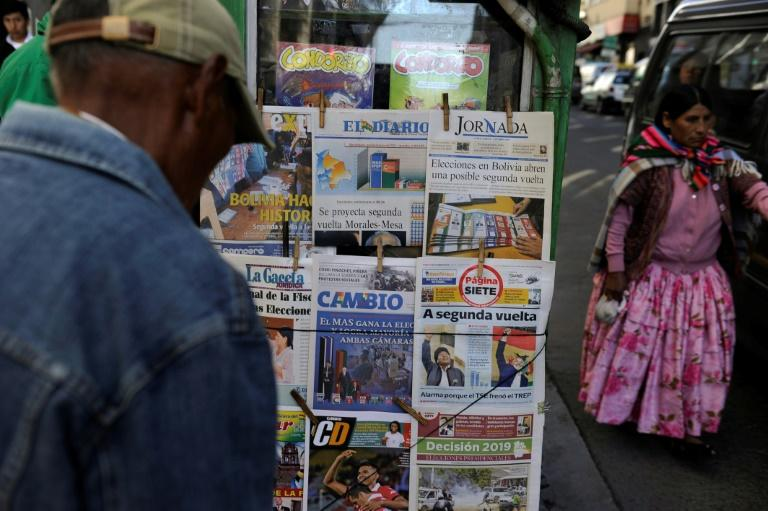 People read the front pages of newspapers Monday in La Paz, Bolivia, after the presidential election (AFP Photo/JORGE BERNAL)