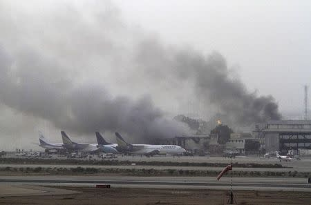 Smoke billows from Jinnah International Airport in Karachi in this June 9, 2014 file photo. Taliban militants attacked Jinnah International Airport in Karachi on Sunday night, sparking a five-hour gun battle that killed at least 34 people. All 10 militants were dead by dawn, shot down by the security forces or blown up by their own suicide vests. REUTERS/Athar Hussain/Files