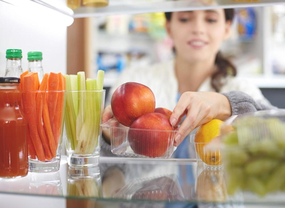 Woman reorganizing her fridge to put fresh fruits vegetables healthy snacks in front