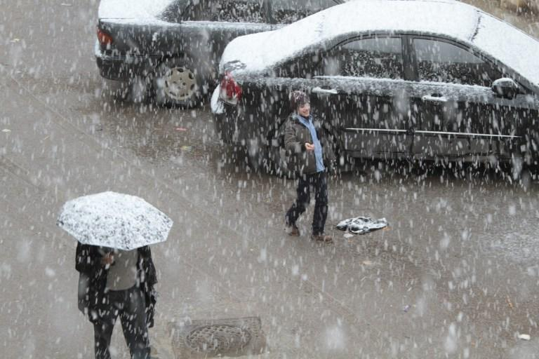 Syrians walk in central Damascus during snow fall on January 9, 2013 as a fierce storm whipped the region this week and temperatures dropped dramatically.   AFP PHOTO/ STR